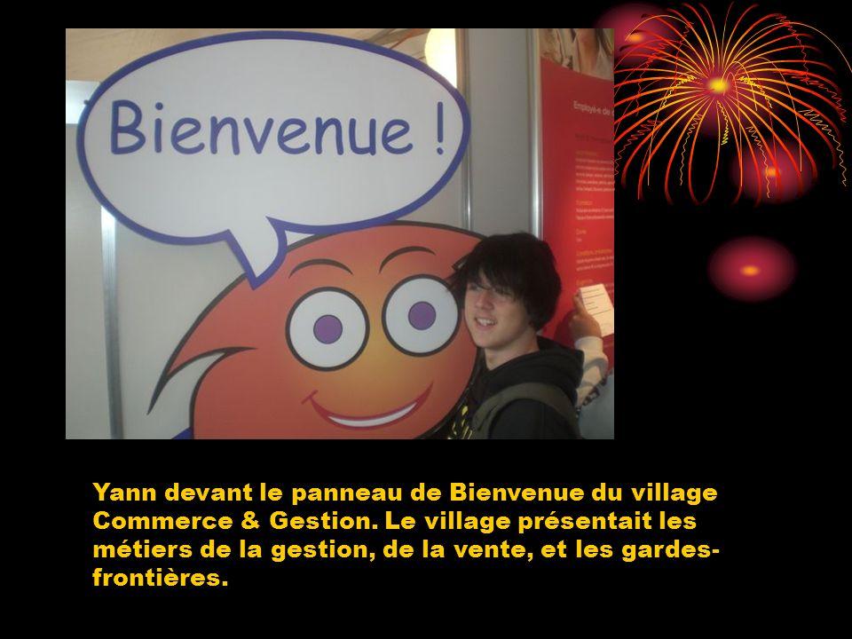 Yann devant le panneau de Bienvenue du village Commerce & Gestion