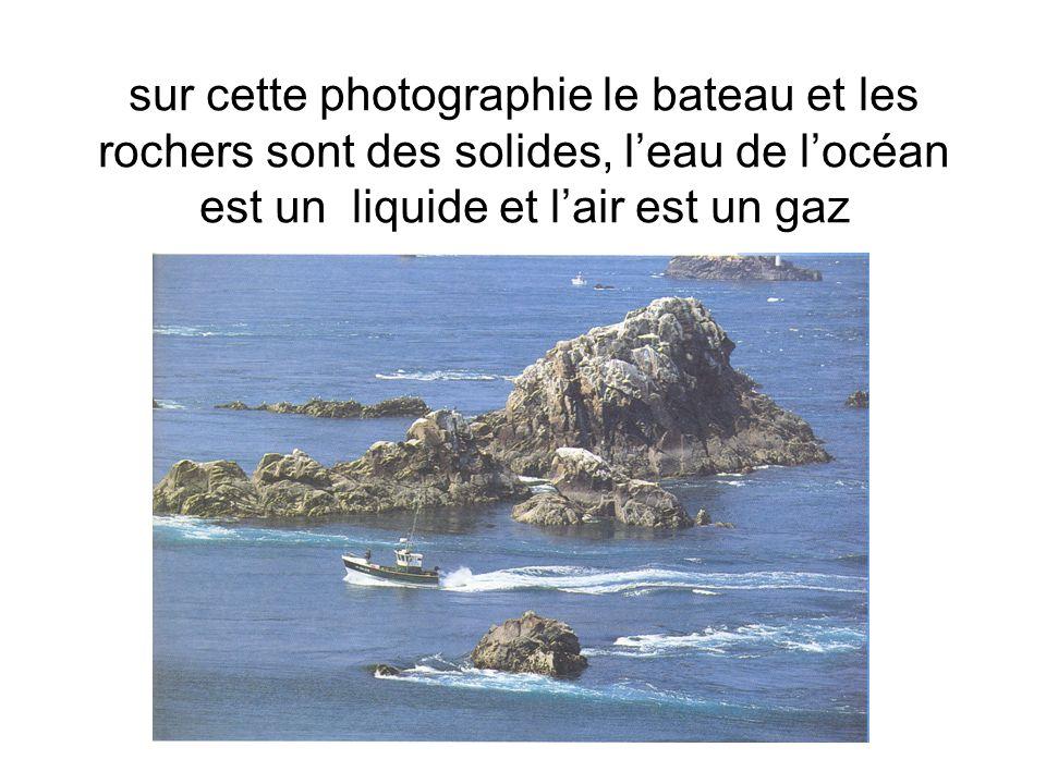 sur cette photographie le bateau et les rochers sont des solides, l'eau de l'océan est un liquide et l'air est un gaz
