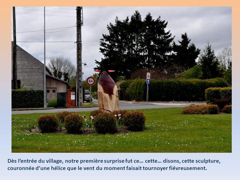Dès l'entrée du village, notre première surprise fut ce… cette… disons, cette sculpture, couronnée d'une hélice que le vent du moment faisait tournoyer fiévreusement.