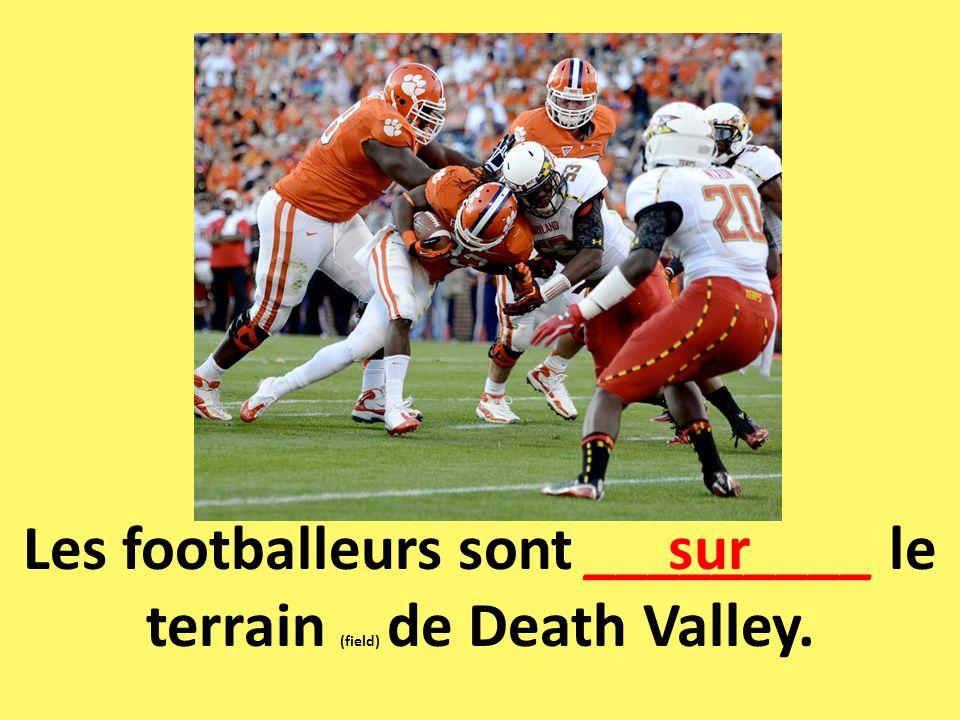 Les footballeurs sont _________ le terrain (field) de Death Valley.