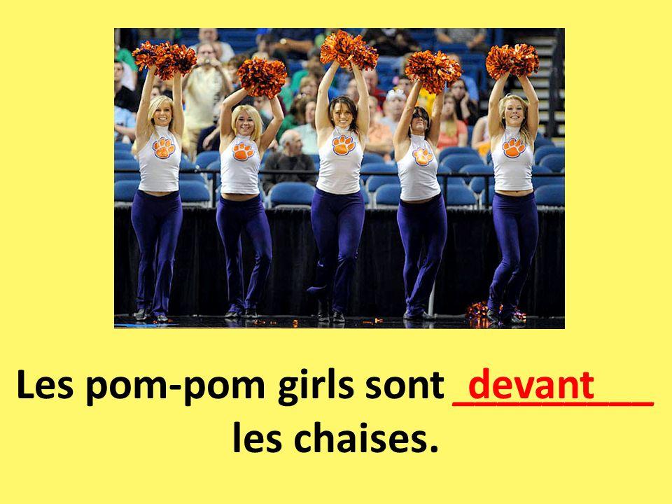 Les pom-pom girls sont _________ les chaises.