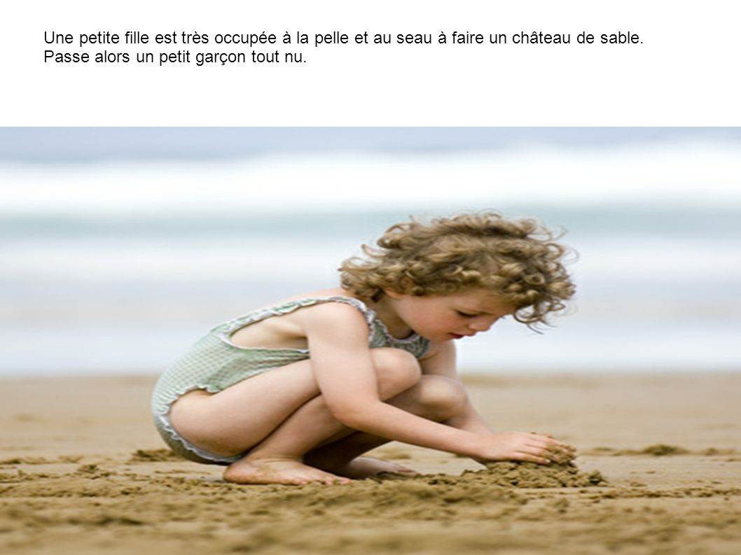 Une petite fille est très occupée à la pelle et au seau à faire un château de sable.