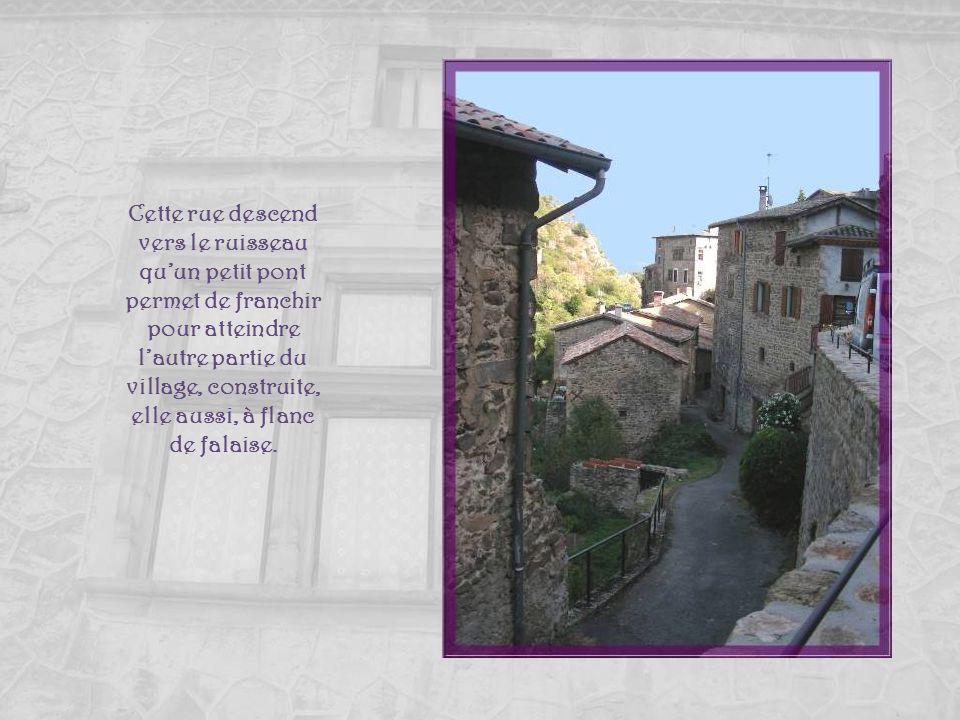 Cette rue descend vers le ruisseau qu'un petit pont permet de franchir pour atteindre l'autre partie du village, construite, elle aussi, à flanc de falaise.