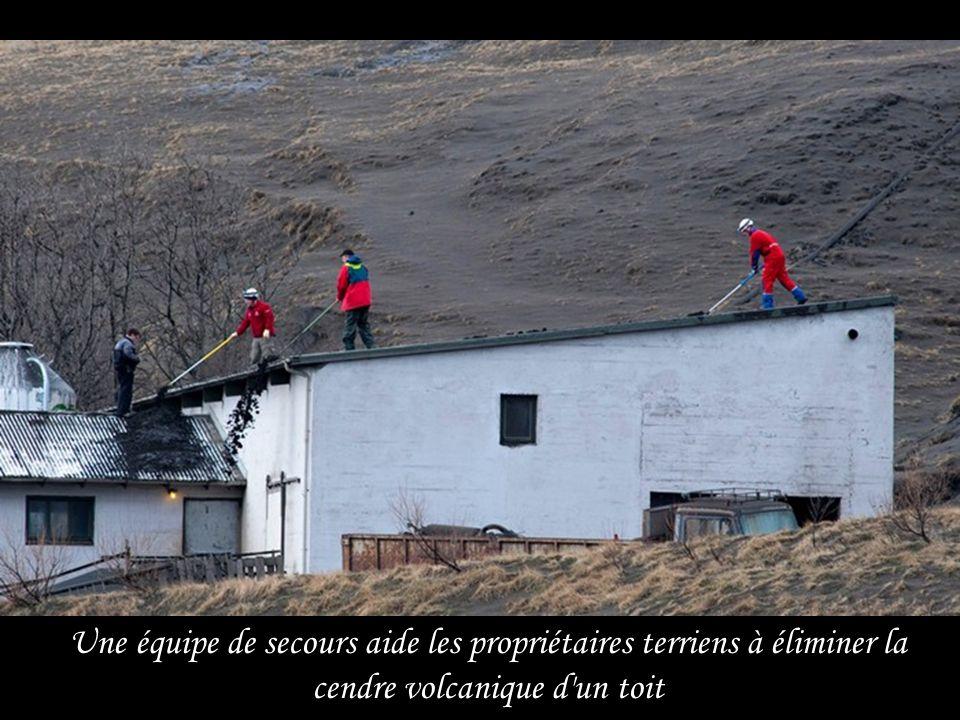 Une équipe de secours aide les propriétaires terriens à éliminer la cendre volcanique d un toit