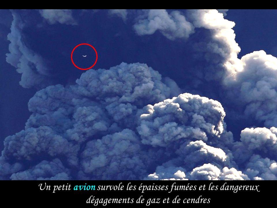 Un petit avion survole les épaisses fumées et les dangereux dégagements de gaz et de cendres