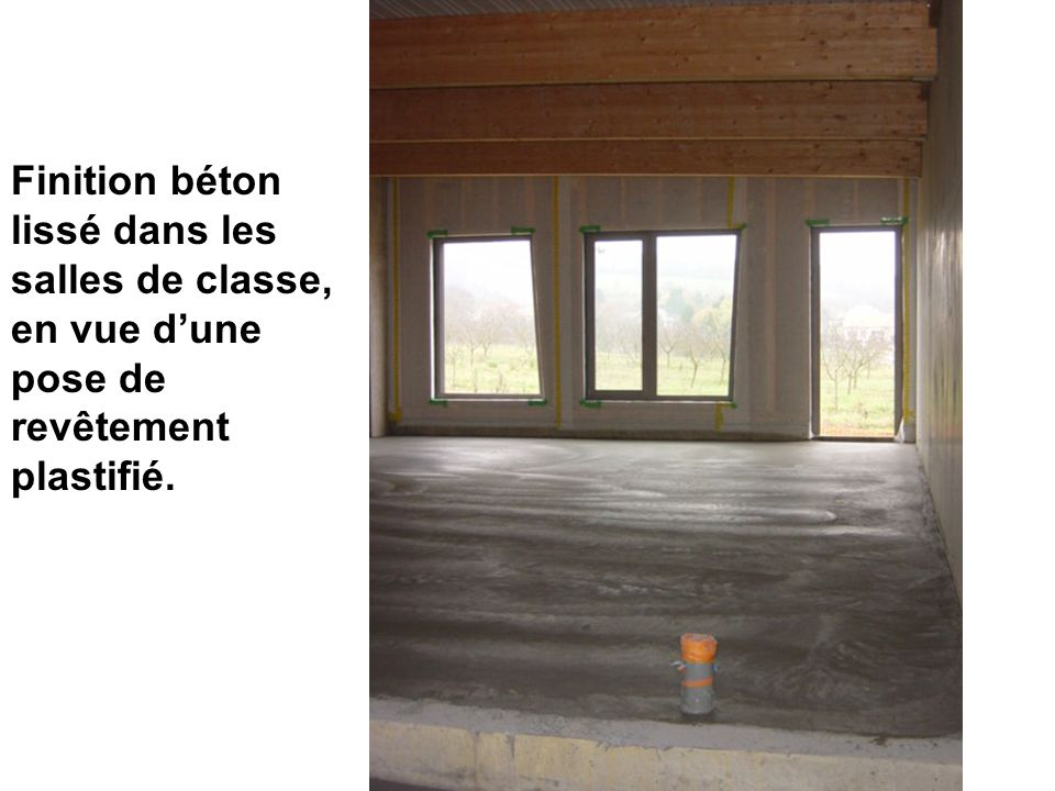 Finition béton lissé dans les salles de classe, en vue d'une pose de revêtement plastifié.