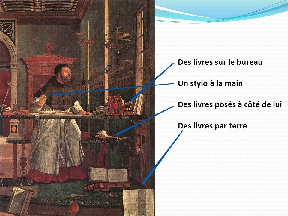 Des livres sur le bureau Un stylo à la main Des livres posés à côté de lui Des livres par terre