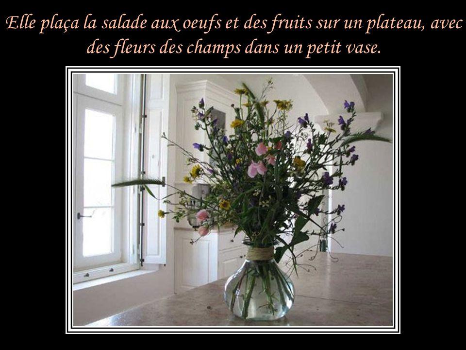Elle plaça la salade aux oeufs et des fruits sur un plateau, avec des fleurs des champs dans un petit vase.
