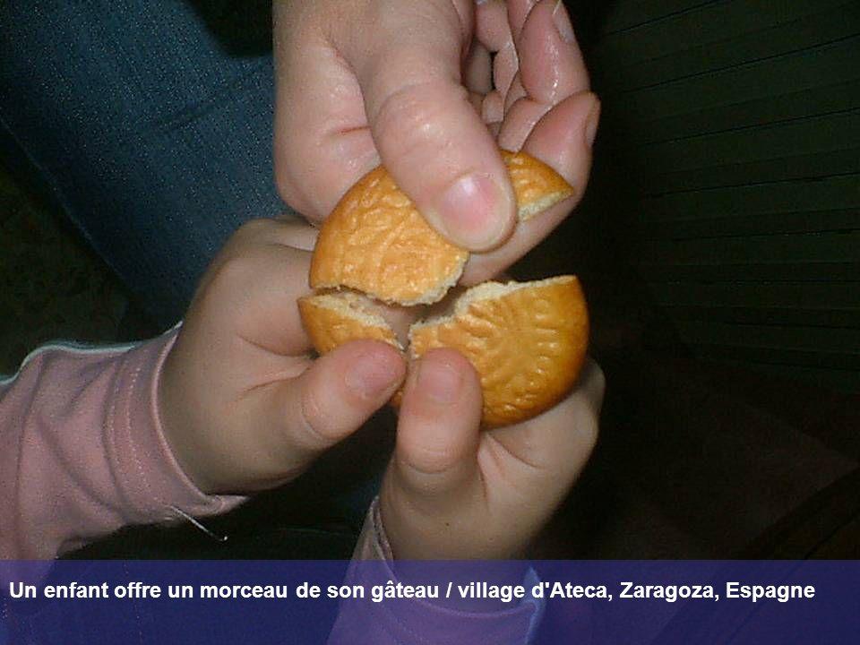 Un enfant offre un morceau de son gâteau / village d Ateca, Zaragoza, Espagne