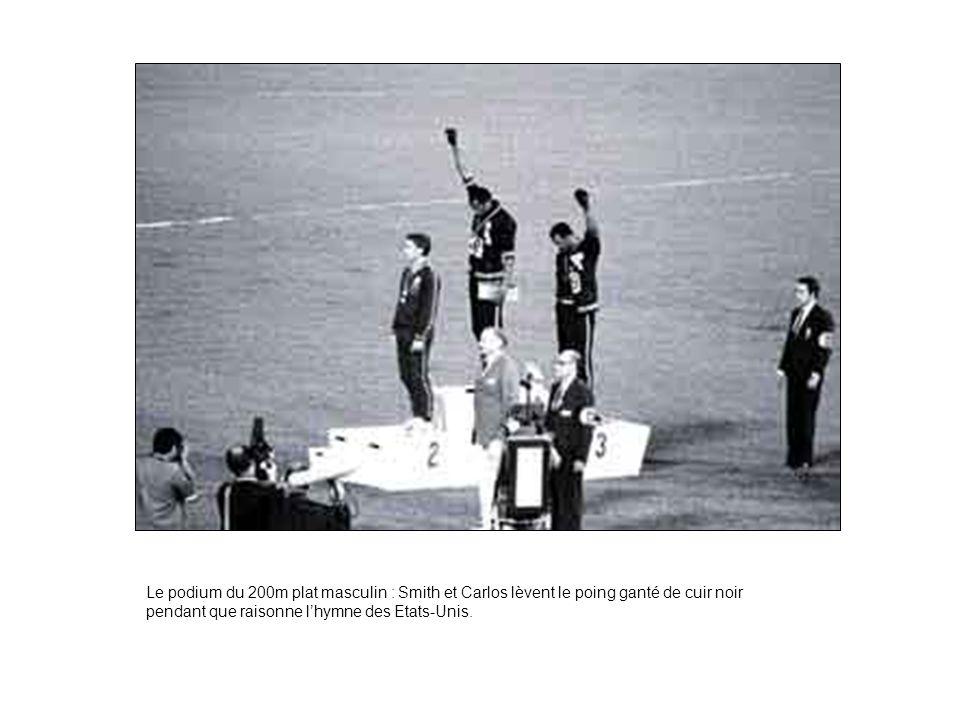 Le podium du 200m plat masculin : Smith et Carlos lèvent le poing ganté de cuir noir pendant que raisonne l'hymne des Etats-Unis.