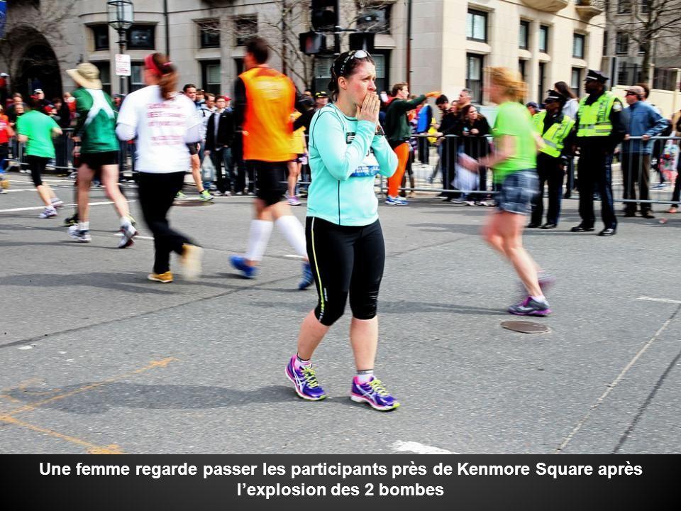 Une femme regarde passer les participants près de Kenmore Square après l'explosion des 2 bombes