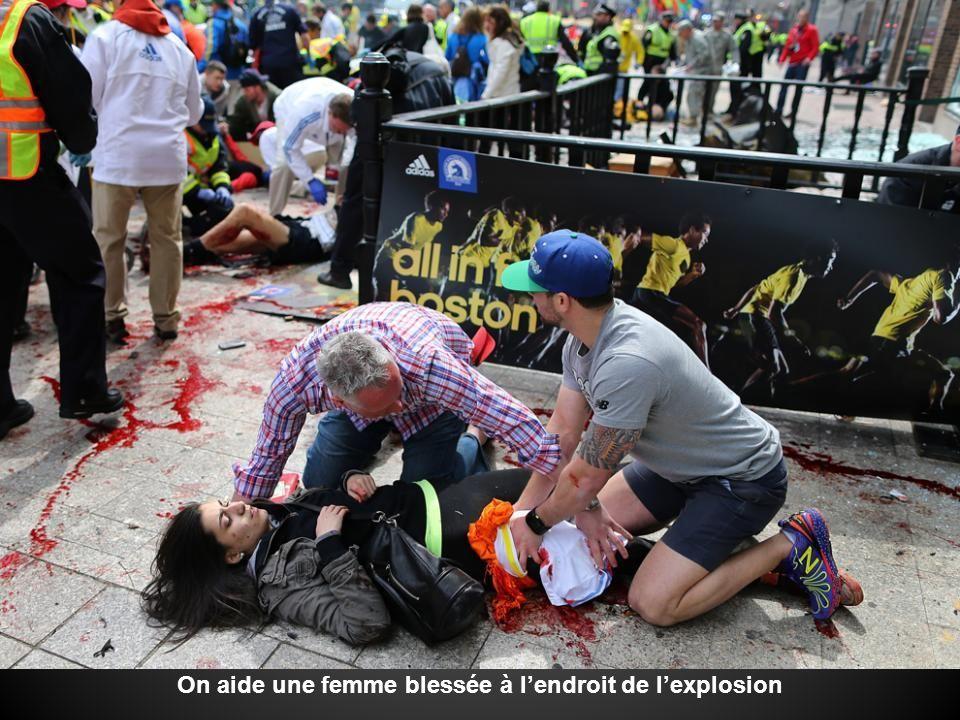 On aide une femme blessée à l'endroit de l'explosion
