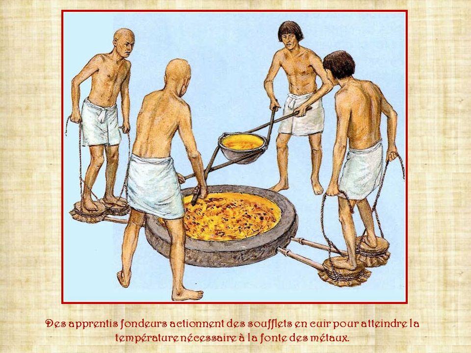 Des apprentis fondeurs actionnent des soufflets en cuir pour atteindre la température nécessaire à la fonte des métaux.