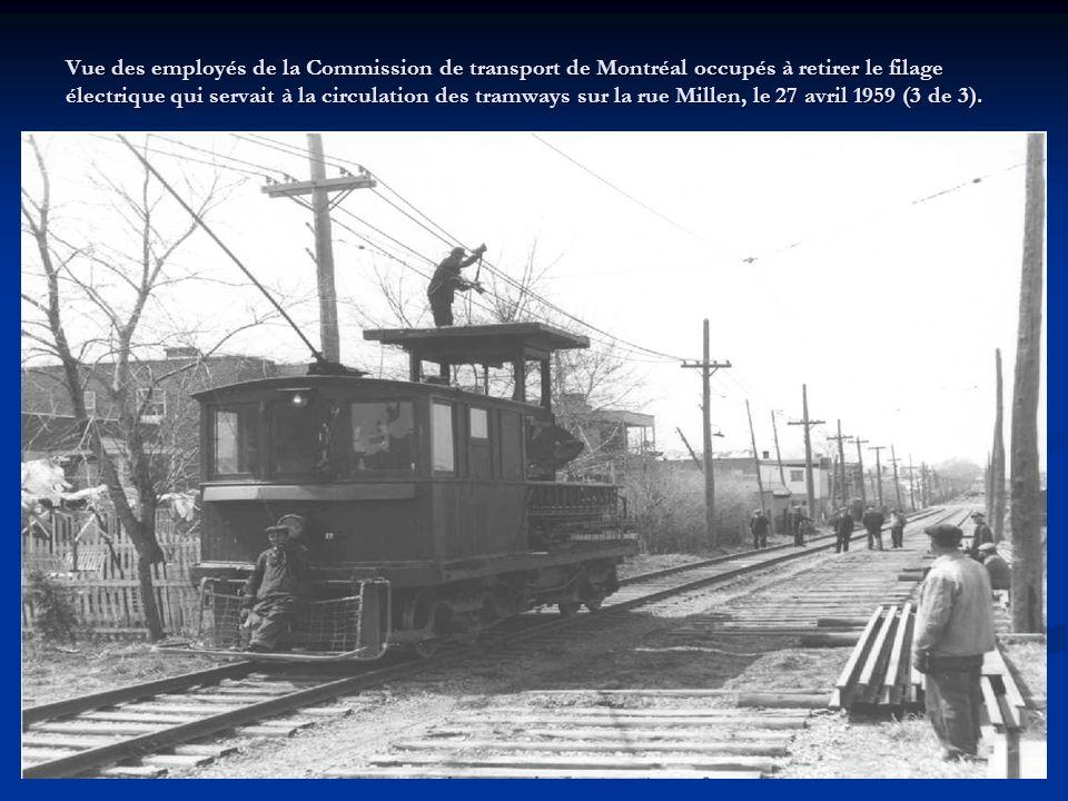 Vue des employés de la Commission de transport de Montréal occupés à retirer le filage électrique qui servait à la circulation des tramways sur la rue Millen, le 27 avril 1959 (3 de 3).