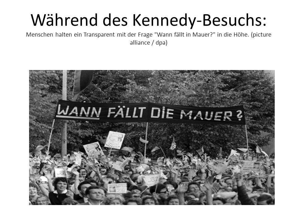 Während des Kennedy-Besuchs: Menschen halten ein Transparent mit der Frage Wann fällt in Mauer in die Höhe.