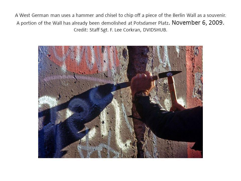 A West German man uses a hammer and chisel to chip off a piece of the Berlin Wall as a souvenir.