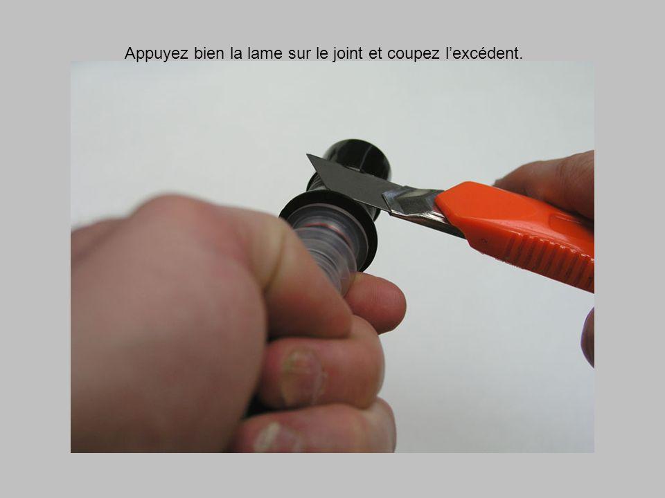 Appuyez bien la lame sur le joint et coupez l'excédent.
