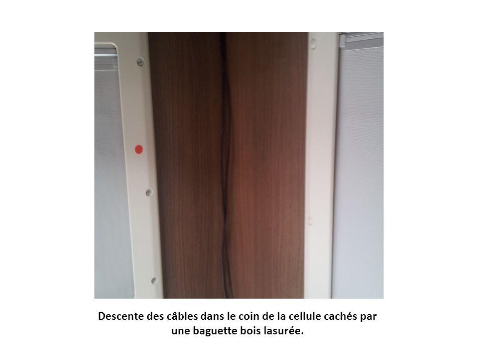 Descente des câbles dans le coin de la cellule cachés par une baguette bois lasurée.