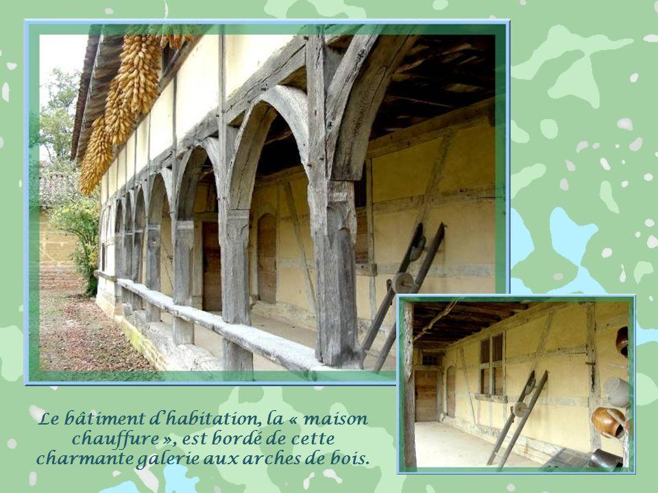 Le bâtiment d'habitation, la « maison chauffure », est bordé de cette charmante galerie aux arches de bois.