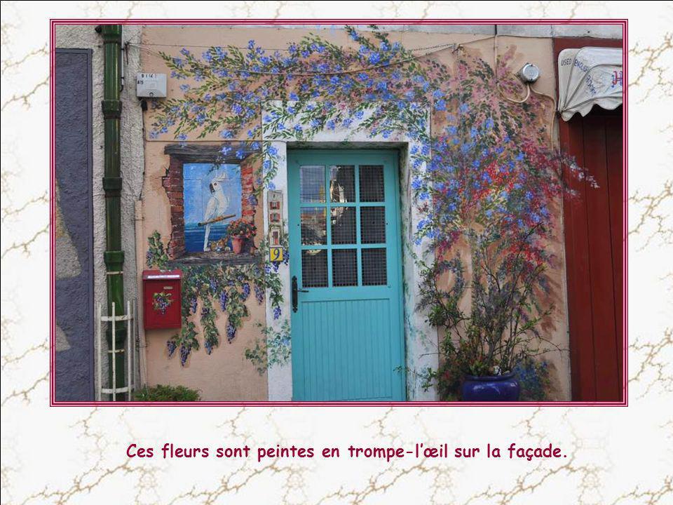 Ces fleurs sont peintes en trompe-l'œil sur la façade.