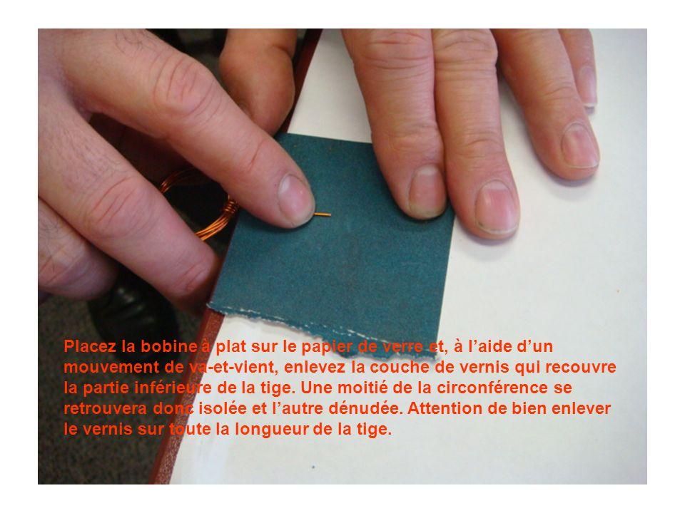 Placez la bobine à plat sur le papier de verre et, à l'aide d'un mouvement de va-et-vient, enlevez la couche de vernis qui recouvre la partie inférieure de la tige.