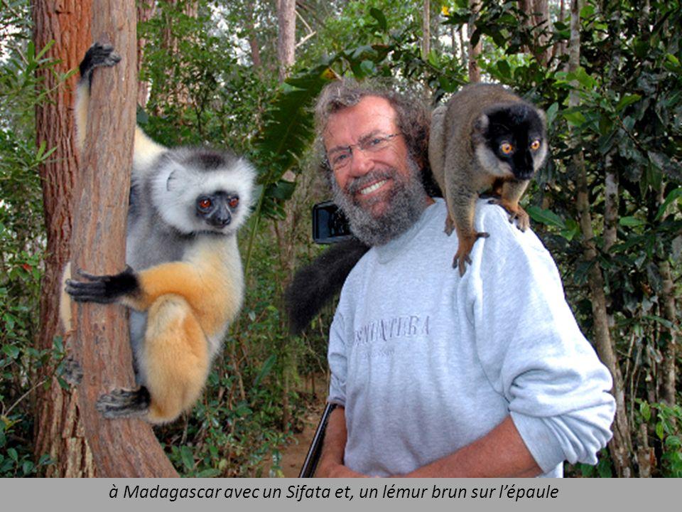 à Madagascar avec un Sifata et, un lémur brun sur l'épaule