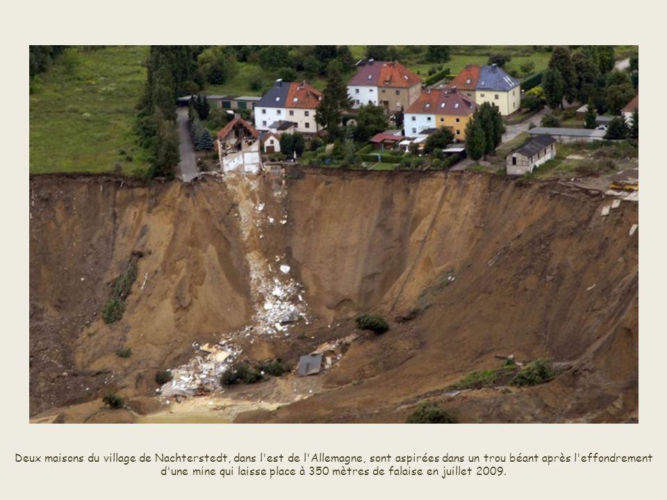 Deux maisons du village de Nachterstedt, dans l est de l Allemagne, sont aspirées dans un trou béant après l effondrement d une mine qui laisse place à 350 mètres de falaise en juillet 2009.
