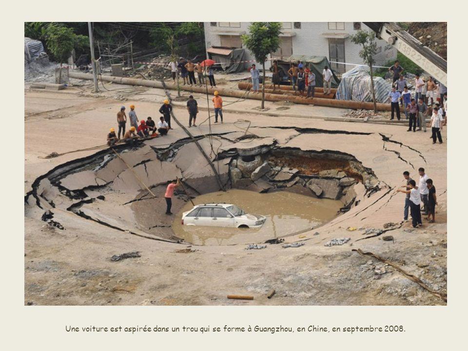 Une voiture est aspirée dans un trou qui se forme à Guangzhou, en Chine, en septembre 2008.