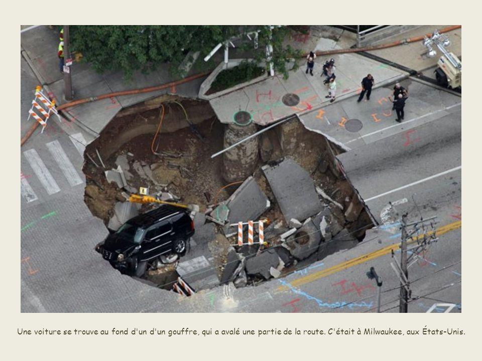 Une voiture se trouve au fond d un d un gouffre, qui a avalé une partie de la route.