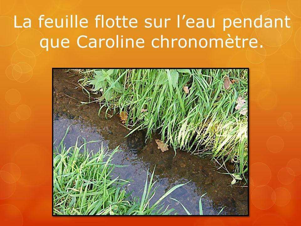 La feuille flotte sur l'eau pendant que Caroline chronomètre.