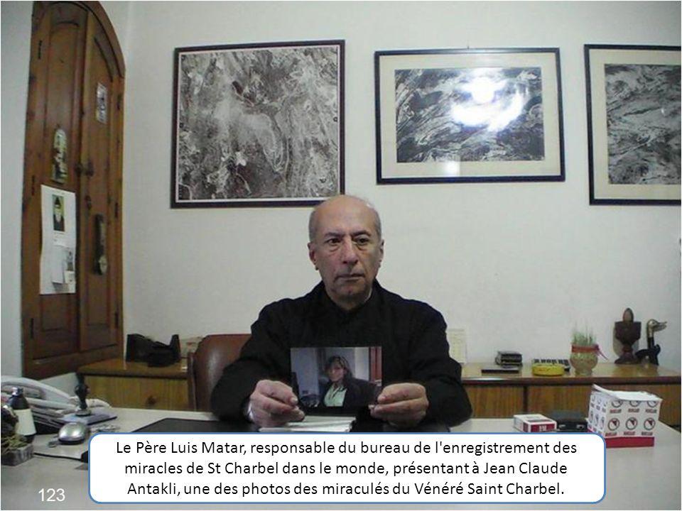 Le Père Luis Matar, responsable du bureau de l enregistrement des miracles de St Charbel dans le monde, présentant à Jean Claude Antakli, une des photos des miraculés du Vénéré Saint Charbel.
