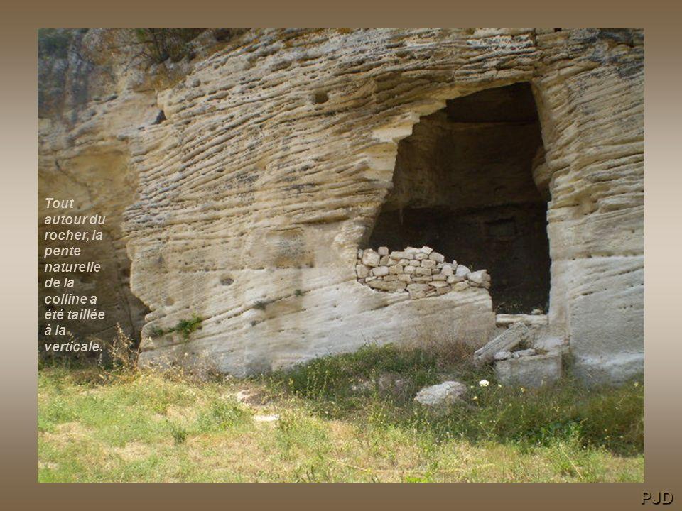 Tout autour du rocher, la pente naturelle de la colline a été taillée à la verticale.