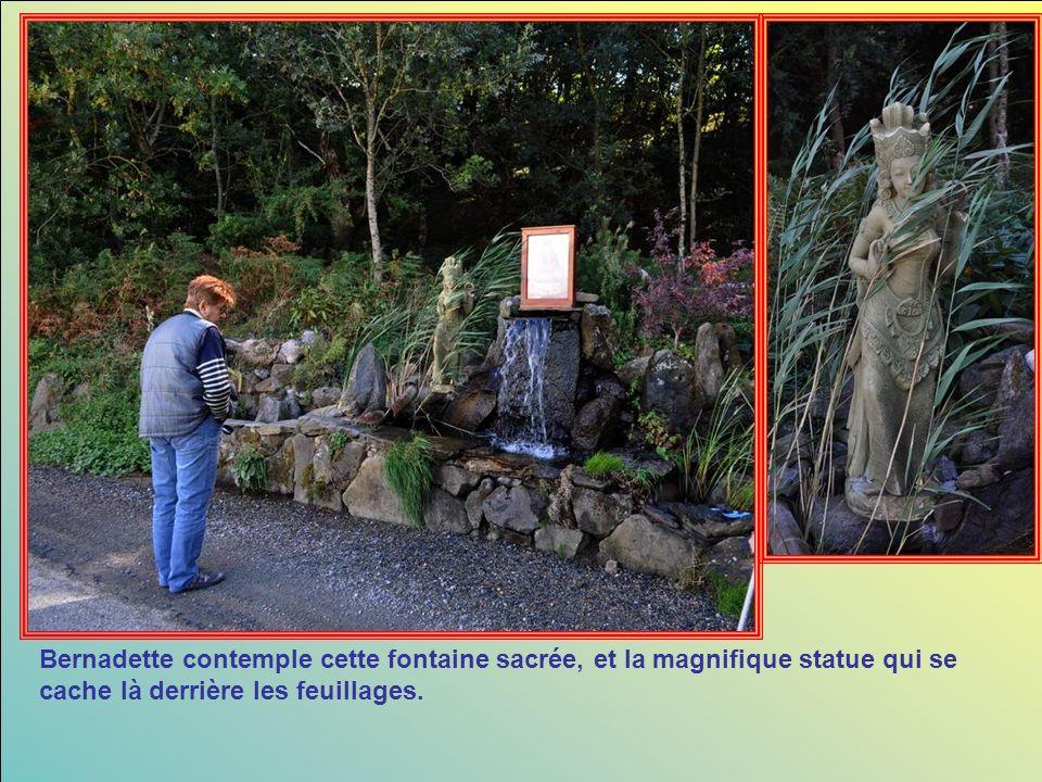 Bernadette contemple cette fontaine sacrée, et la magnifique statue qui se cache là derrière les feuillages.
