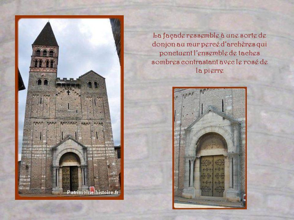La façade ressemble à une sorte de donjon au mur percé d'archères qui ponctuent l'ensemble de taches sombres contrastant avec le rosé de la pierre