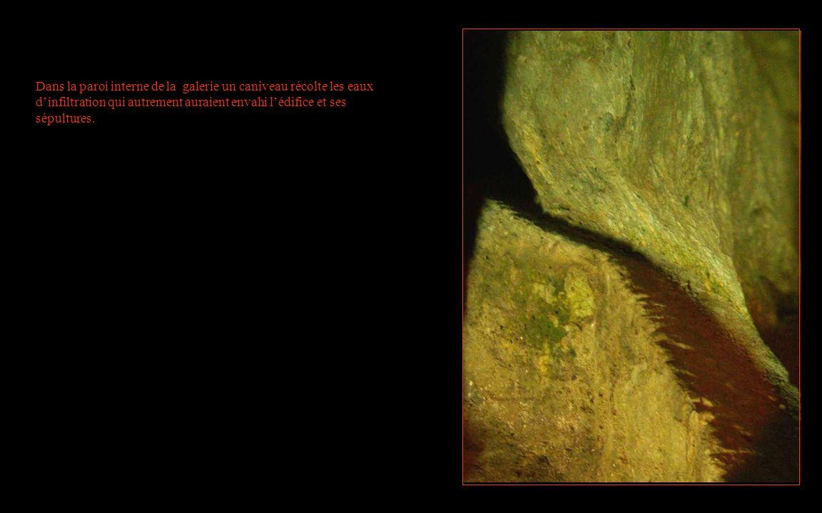 Dans la paroi interne de la galerie un caniveau récolte les eaux d'infiltration qui autrement auraient envahi l'édifice et ses sépultures.