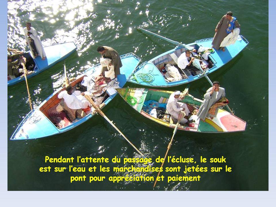 Pendant l'attente du passage de l'écluse, le souk est sur l'eau et les marchandises sont jetées sur le pont pour appréciation et paiement