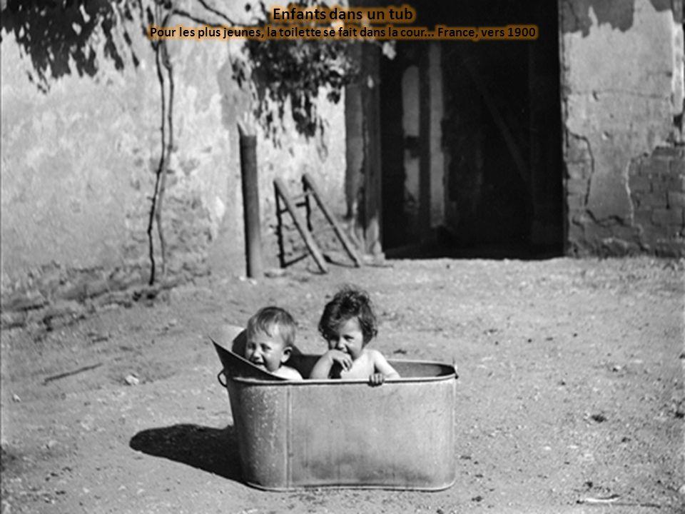 Enfants dans un tub Pour les plus jeunes, la toilette se fait dans la cour... France, vers 1900