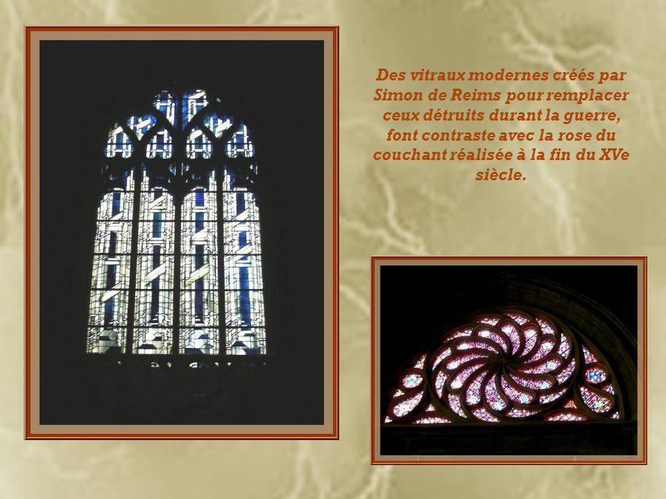 Des vitraux modernes créés par Simon de Reims pour remplacer ceux détruits durant la guerre, font contraste avec la rose du couchant réalisée à la fin du XVe siècle.