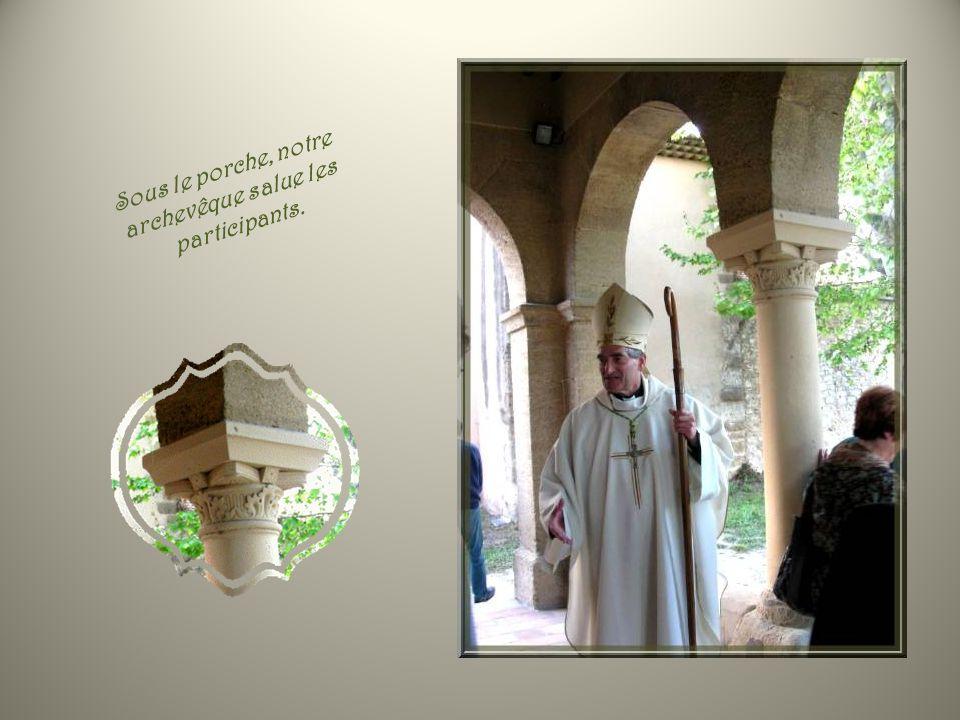 Sous le porche, notre archevêque salue les participants.