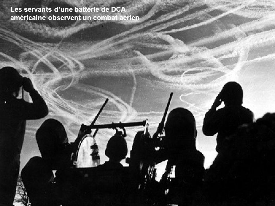 Les servants d'une batterie de DCA américaine observent un combat aérien