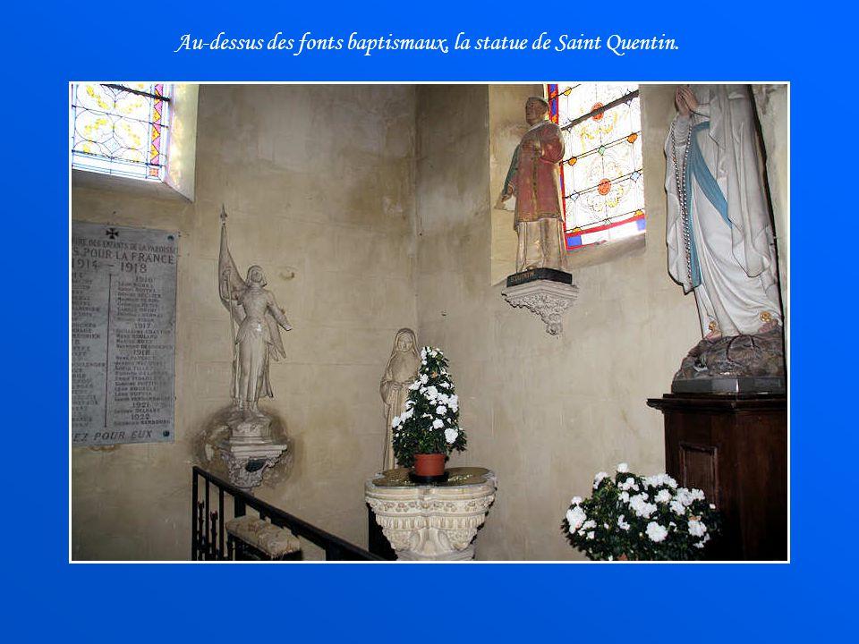 Au-dessus des fonts baptismaux, la statue de Saint Quentin.