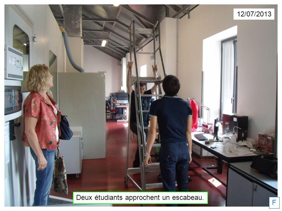 Deux étudiants approchent un escabeau.