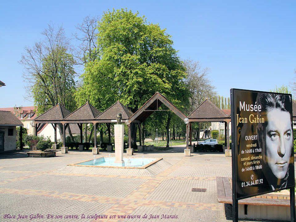 Place Jean Gabin. En son centre, la sculpture est une œuvre de Jean Marais.
