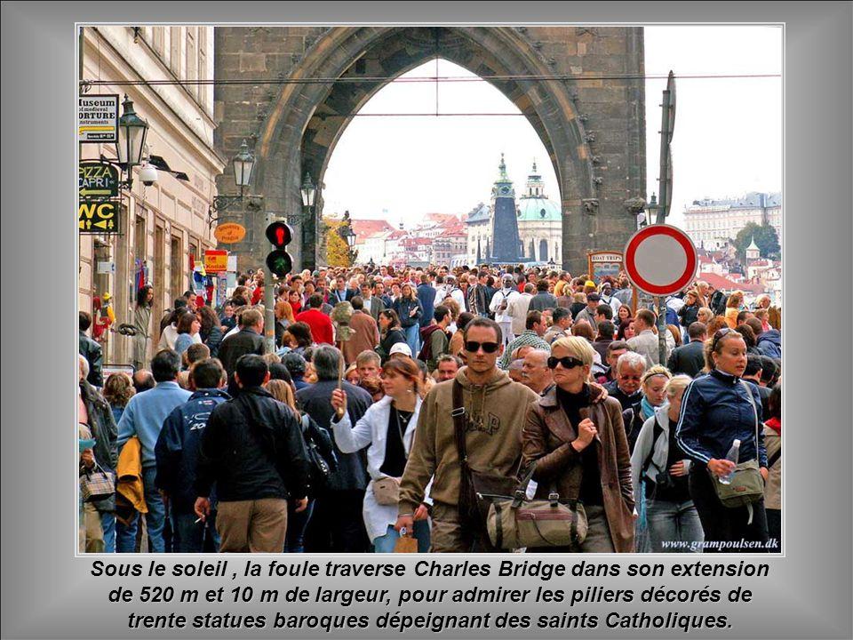 Sous le soleil , la foule traverse Charles Bridge dans son extension de 520 m et 10 m de largeur, pour admirer les piliers décorés de trente statues baroques dépeignant des saints Catholiques.
