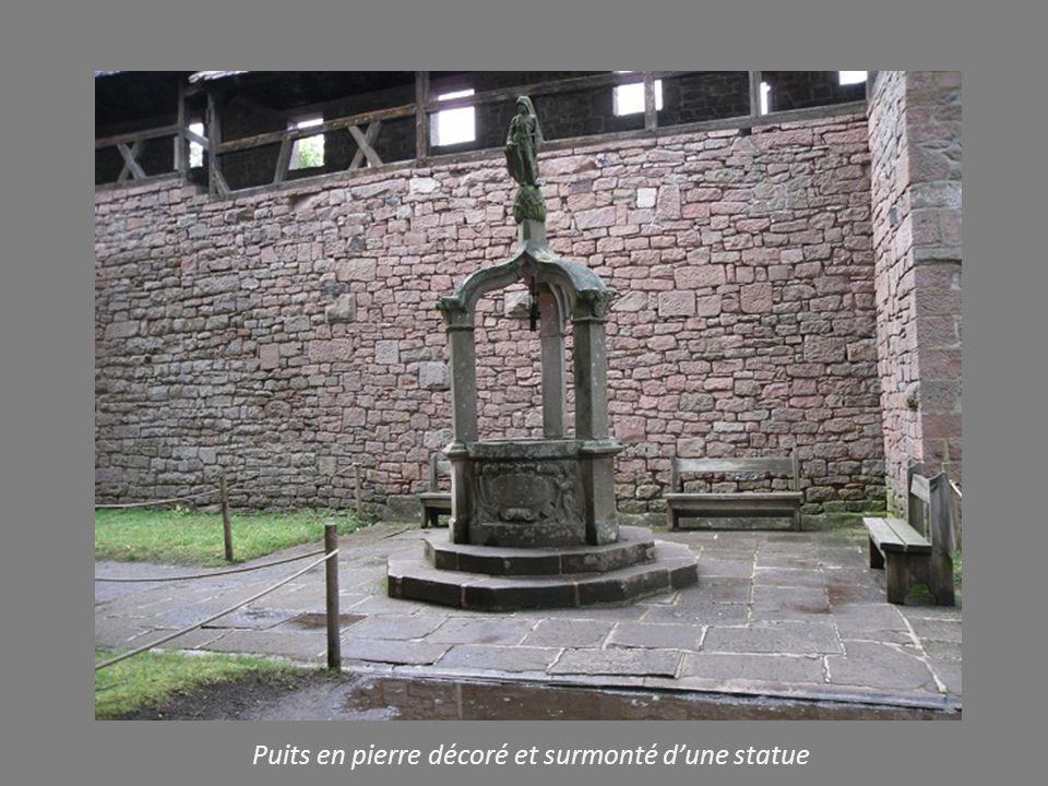 Puits en pierre décoré et surmonté d'une statue