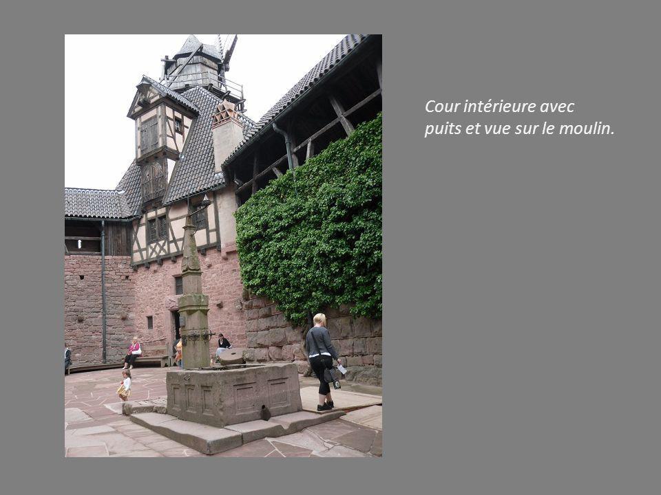 Cour intérieure avec puits et vue sur le moulin.