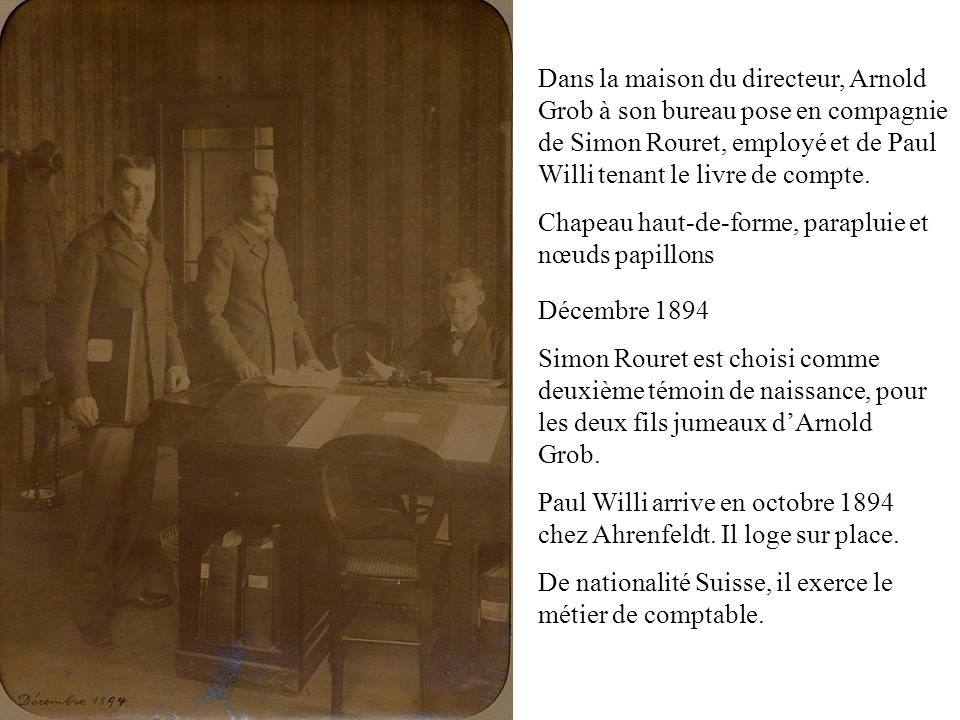 Dans la maison du directeur, Arnold Grob à son bureau pose en compagnie de Simon Rouret, employé et de Paul Willi tenant le livre de compte.