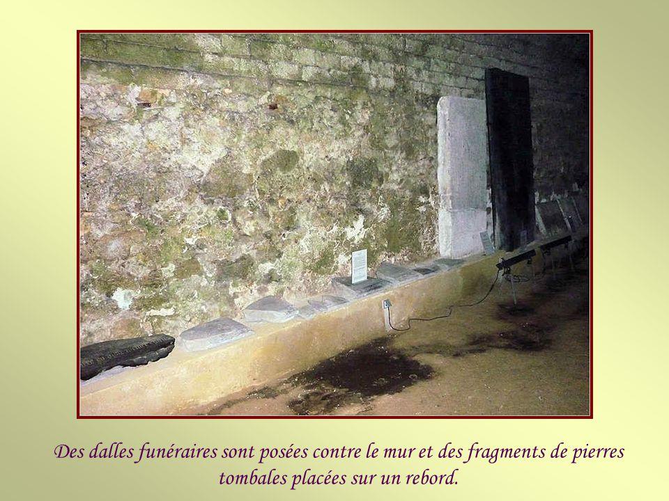 Des dalles funéraires sont posées contre le mur et des fragments de pierres tombales placées sur un rebord.