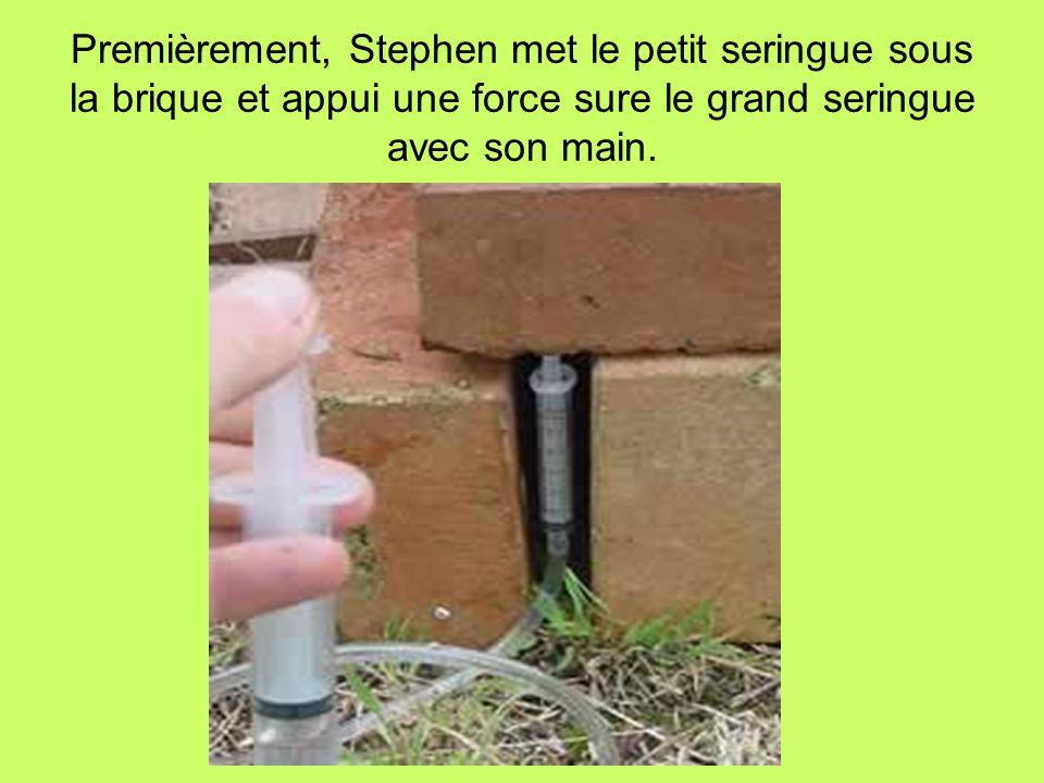 Premièrement, Stephen met le petit seringue sous la brique et appui une force sure le grand seringue avec son main.