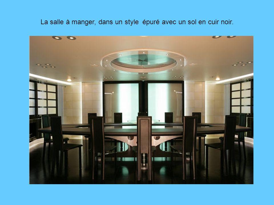 La salle à manger, dans un style épuré avec un sol en cuir noir.